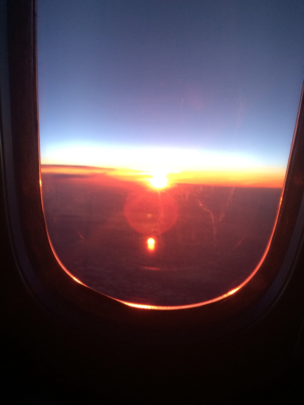 Photo of a sunrise from an airplane window