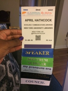 April's conference badge with ribbons for Speaker, Spectrum Scholar, pronouns she/her/hers, Wakanda Research Library Staff, and Council