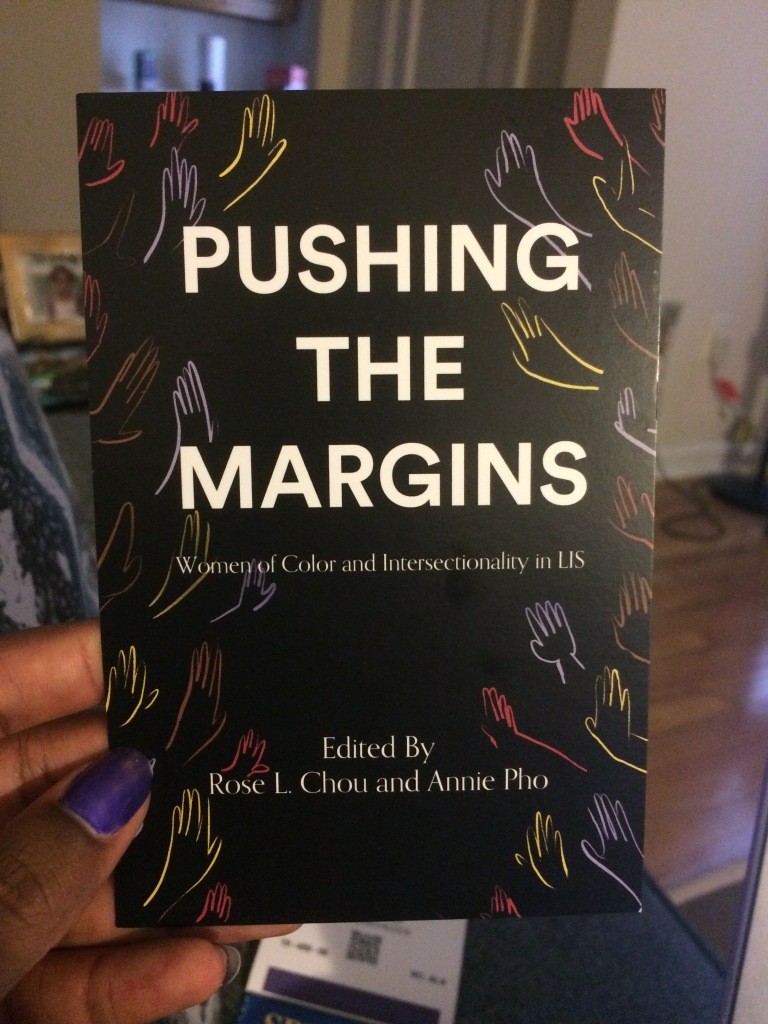 "black postcard with multicolored hand outlines in background titled ""Pushing the Margins: Women of Color and Intersectionality in LIS,"" edited by Rose L. Chou and Annie Pho"