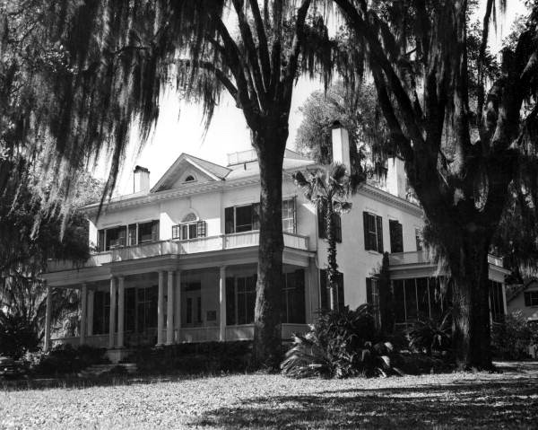 Black and white image of a large plantation house surrounded by Spanish moss and oak trees
